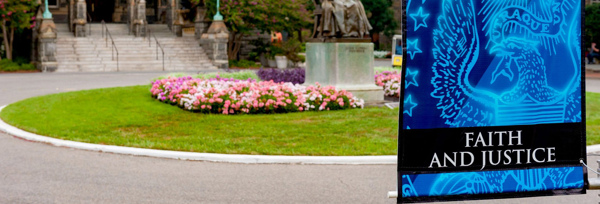 Image of John Carroll Statue, in front of Healy Hall, surrounded by flowering plants. In the foreground a banner with the words